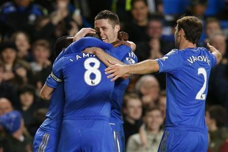 Frank Lampard (8) of Chelsea is congratulated by teammates Gary Cahill (2nd R), Branislav Ivanonic (R) and Victor Moses (obscured) after scoring his team's fourth goal against Aston Villa during their English Premier League soccer match at Stamford Bridge, London December 23, 2012. REUTERS/Andrew Winning