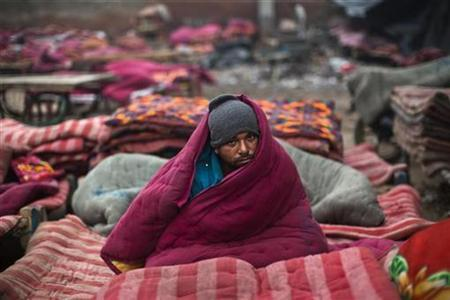 A homeless man, wrapped in a quilt, sits in an open space on a cold winter morning in the old quarters of Delhi January 3, 2013. REUTERS/Ahmad Masood