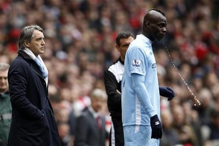 Manchester City's Mario Balotelli (R) spits water next to manager Roberto Mancini during their English Premier League soccer match against Arsenal at the Emirates Stadium in London April 8, 2012. REUTERS/Stefan Wermuth/Files