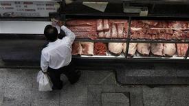 Foto de archivo de un cliente frente a una carnicería en el mercado municipal de Sao Paulo, feb 4 2012. El índice de precios al productor de Brasil se aceleró en noviembre y mostró un alza del 0,25 por ciento influenciado por el sector de alimentos y el de fabricación de productos de madera. REUTERS/Nacho Doce