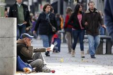 A man begs as pedestrians walk past at Wilmersdorfer shopping street in Berlin October 9, 2012. REUTERS/Fabrizio Bensch