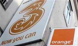 "The logos of ""Orange"" and ""3"" are pictured outside a telecommunications store in Vienna February 3, 2012. REUTERS/Heinz-Peter Bader"
