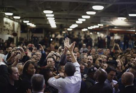U.S. President Barack Obama high-fives an employee of the Daimler Detroit Diesel plant following remarks and a tour in Redford, Michigan, December 10, 2012. REUTERS/Jason Reed