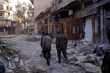 Forces loyal to Syria's President Bashar al-Assad walk on the rubble of damaged buildings and shops in the old city of Aleppo January 3, 2013. REUTERS/George Ourfalian
