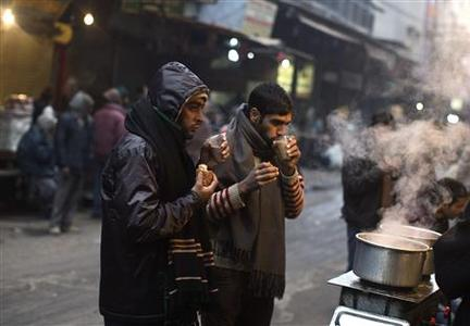 People drink tea at a roadside tea stall on a cold winter morning in the old quarters of Delhi January 3, 2013. REUTERS/Ahmad Masood