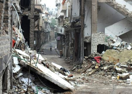 A man walks along a damaged street in the city of Homs January 1, 2013. Picture taken January 1, 2013. REUTERS/Yazan Homsy