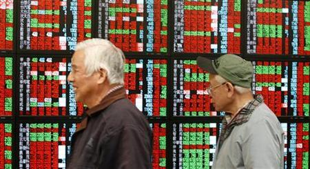 A man smiles near another man monitoring stock market prices inside a brokerage in Taipei January 3, 2013. REUTERS/Pichi Chuang