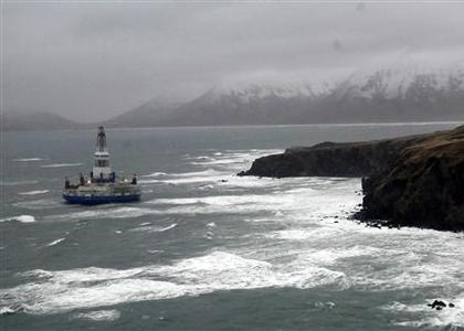The conical drilling unit Kulluk, owned by Royal Dutch/Shell, sits aground 40 miles (64 kms) southwest of Kodiak City, Alaska, on the shore of Sitkalidak Island in this U.S. Coast Guard handout photo taken January 2, 2013. The Kulluk ran aground on New Year's Eve in ''near hurricane'' conditions and dragged two vessels trying to control it more than 10 miles toward Sitkalidak Island before the crews cut it loose to save themselves, the U.S. Coast Guard said. REUTERS/U.S. Coast Guard/Petty Officer 1st Class Travis Marsh/Handout
