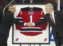 "New Jersey Devils TV announcer Mike ""Doc"" Emrick shakes hands with Devils owner Jeff Vanderbeek (R) as he is presented a framed jersey while being honored by the team prior to their NHL hockey game with the Vancouver Canucks in Newark, New Jersey, February 24, 2012. REUTERS/Ray Stubblebine"
