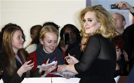 Multiple Grammy Award winner Adele signs autographs as she arrives for the BRIT Music Awards at the O2 Arena in London February 21, 2012. REUTERS/Luke MacGregor/Files
