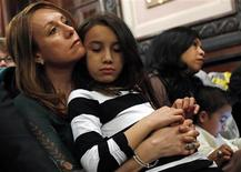 Theresa Volpe (L) holds her daughter Ava (2nd L) as her partner Mercedes Santos sits with their son Jaidon after testifying at the Illinois State Capital in Springfield, Illinois, January 3, 2013. Volpe and Santos have been together for 21 years and are in a civil union and have two children. Illinois could become the next U.S. state to legalize gay marriage with a bill set to be introduced in the state Senate this week. REUTERS/Jim Young