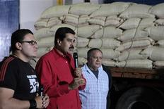 Venezuela's Vice President Nicolas Maduro (C) speaks next to Venezuelan National Assembly President Diosdado Cabello (R) and Agriculture Minister Juan Carlos Loyo, during a visit to Fama de America's coffee processing plant in Caracas January 3, 2013. Maduro returned to Venezuela on Thursday after visiting Hugo Chavez in hospital in Cuba, but gave no new details on the cancer-stricken president as rumours grow about his condition. REUTERS/Miraflores Palace/Handout