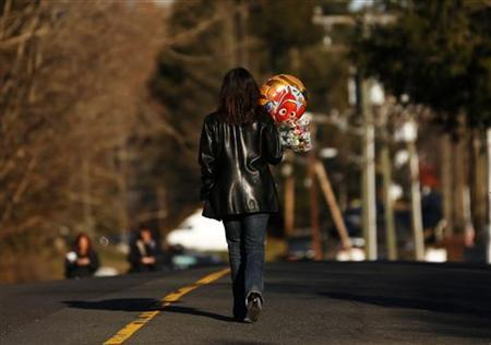 A woman walks with a balloon to a makeshift memorial of flowers and balloons next to the Sandy Hook Elementary school sign in Connecticut December 15, 2012. REUTERS/Shannon Stapleton