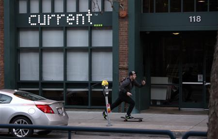 A man rides a skateboard in front of Current TV in San Francisco, California January 3, 2013. English-language satellite news channel Al Jazeera said it will buy Current TV, the struggling cable channel founded by Al Gore and partners, in a move that will boost the Qatar-based broadcaster's footprint in the United States. REUTERS/Robert Galbraith