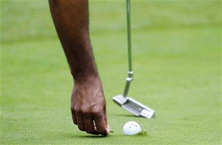 Tiger Woods of the U.S. marks his ball on the 16th green during the final round of the World Challenge golf tournament in Thousand Oaks, California, December 2, 2012. REUTERS/Danny Moloshok