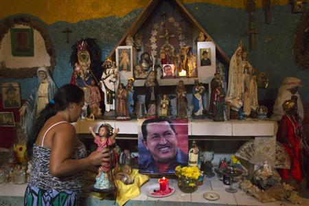 Nancy Romero places a figurine on a religious altar with images of Venezuela's President Hugo Chavez in Caracas January 3, 2013. REUTERS/Carlos Garcia Rawlins