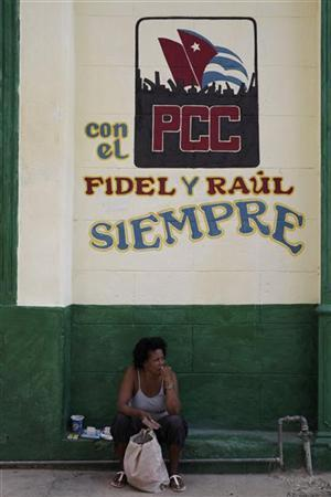 A private vendor sits under a graffiti that reads ''With the Cuban Communist Party Fidel and Raul, forever'' in Havana October 21, 2012. REUTERS/Enrique De La Osa