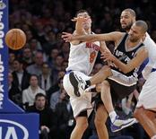 San Antonio Spurs guard Tony Parker (C) slams into New York Knicks guard Pablo Prigioni (L) as he passes in the first quarter of their NBA basketball game at Madison Square Garden in New York January 3, 2013. REUTERS/Ray Stubblebine