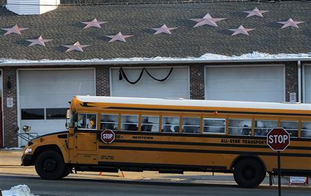 A school bus returning with kids from the new Sandy Hook School passes the fire station with stars on the roof to honor those killed in the shooting, in Sandy Hook, Connecticut, January 3, 2013. REUTERS/Carlo Allegri