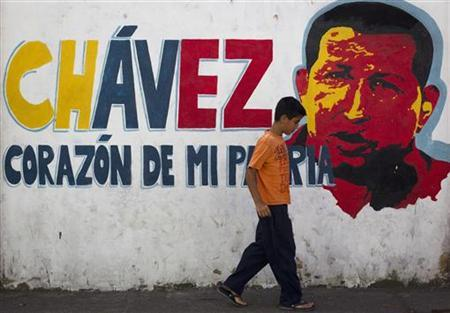A child walks past a mural depicting Venezuelan President Hugo Chavez in Caracas January 3, 2013. REUTERS/Carlos Garcia Rawlins (VENEZUELA - Tags: POLITICS HEALTH RELIGION SOCIETY)