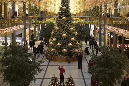 People walk in a shopping mall that is decorated with Christmas lights in Berlin, December 23, 2012. REUTERS/Thomas Peter (GERMANY - Tags: SOCIETY)