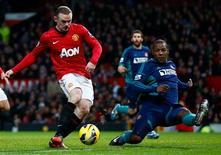 El entrenador del Manchester United, Alex Ferguson, ha aplazado el regreso de Wayne Rooney al terreno de juego tras su lesión, indicando que el delantero estará otras dos semanas de baja. En la imagen, el jugador del Manchester United Wayne Rooney (a la izquierda) pasa junto al jugador del Sunderland Titus Bramble, en su partido de Premier League en Old Trafford, en Manchester, el 15 de diciembre de 2012. REUTERS/Darren Staples