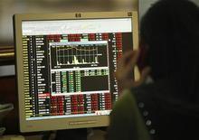 Una trader parla al telefono monitorando al computer l'andamanto del mercato azionario alla Borsa di Kuala Lumpur. REUTERS/Bazuki Muhammad