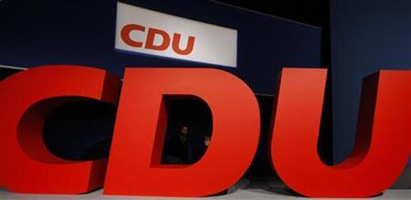 German Chancellor and leader of Germany's conservative Christian Democratic Union (CDU) Angela Merkel looks thourgh a letter of the CDU logo during a party meeting in Leipzig, November 14, 2011. REUTERS/ (GERMANY - Tags: POLITICS BUSINESS LOGO)