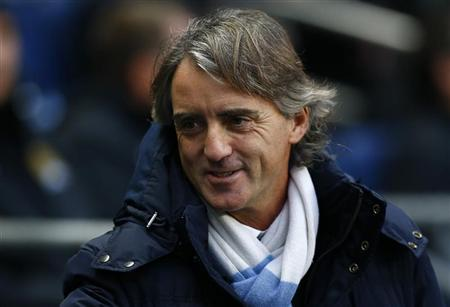Manchester City's manager Roberto Mancini smiles as he takes his seat before their English Premier League match against Reading in Manchester, northern England, December 22, 2012. REUTERS/Darren Staples