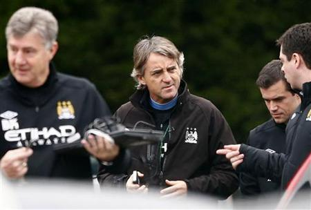 Manchester City's manager Roberto Mancini (C) arrives for a training session at the Carrington training facility in Manchester, northern England, January 4, 2013. REUTERS/Darren Staples