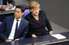 German Chancellor Angela Merkel and Leader of Germany's liberal Free Democrats FDP and Economy Minister Philipp Roesler attend a session of the lower house of parliament Bundestag in Berlin November 9, 2012. REUTERS/Tobias Schwarz