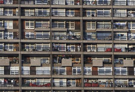 A woman sits on her balcony (TOP RIGHT) in a tower block in west London January 22, 2009. REUTERS/Toby Melville