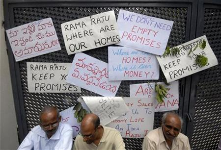 Investors sit outside the house of Ramalinga Raju, founder and former chairman of Satyam Computer Services, during a protest in Hyderabad July 10, 2009. REUTERS/Krishnendu Halder/Files