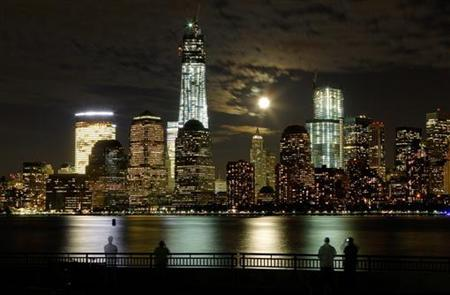 The moon rises behind the skyline of New York's Lower Manhattan and One World Trade Center as people stand along the Hudson River in Jersey City, New Jersey, October 1, 2012. REUTERS/Gary Hershorn