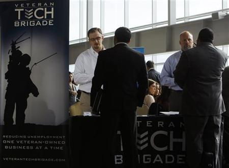 Tom Waterworth (L) and Kelly Crigger (2nd R) of Veteran Tech Brigade, talk to applicants at a job fair for veterans and their spouses held by the U.S. Chamber of Commerce and the Washington Nationals baseball club at Nationals Park in Washington December 5, 2012. REUTERS/Gary Cameron/Files