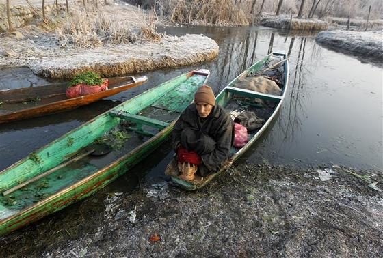 A vegetable vendor sits on his boat as he warms himself using 'Kangri', or a traditional fire pot, on a cold winter morning in Srinagar January 4, 2013. The coldest weather in northern India for at least 44 years has killed more than 100 homeless people, an aid group said on Thursday. REUTERS/Danish Ismail