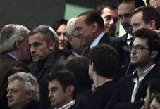 Silvio Berlusconi (au centre) dans les tribunes de San Siro. Les joueurs du Milan AC quitteront le terrain chaque fois qu'ils entendront des chants racistes monter des tribunes, a prévenu vendredi l'ancien président du Conseil italien, également propriétaire du club. /Photo prise le 25 février 2012/REUTERS/Stefano Rellandini