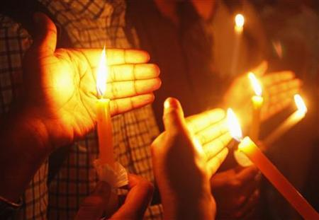 Participants hold candles as they sing during a vigil for the rape victim, who passed away last Friday, in Singapore January 2, 2013. REUTERS/Edgar Su