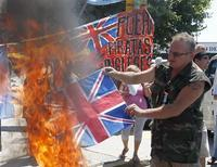 "A British flag is set on fire during a protest by left-wing activists at the Buenos Aires cruise terminal January 4, 2013. Britain's biggest-selling newspaper had a simple message for Argentina in an editorial published on Friday in the South American country: ""HANDS OFF"" the Falkland Islands. The sign on the back reads: ""Get out British pirates"". REUTERS/Enrique Marcarian"