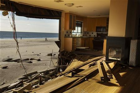 A couple walks their dog on a beach framed by a home damaged by superstorm Sandy two months after the storm caused extensive damage in the Queens borough region of Belle Harbor, New York, December 28, 2012. REUTERS/Lucas Jackson