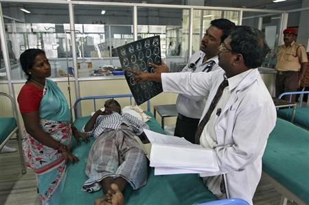 Doctors examine a magnetic resonance imaging (MRI) scan of a patient lying on a bed inside a ward at Rajiv Gandhi Government General Hospital (RGGGH) in Chennai July 12, 2012. REUTERS/Babu