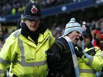 Un supporter de Manchester City, ici lors de son arrestation, qui avait pénétré sur le terrain pour agresser Rio Ferdinand durant le derby contre Manchester United a été interdit de stade pour une durée de trois ans vendredi par un tribunal. /Photo prise le 9 décembre 2012/REUTERS/Phil Noble