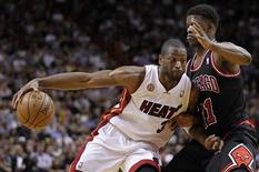 Miami Heat's Dwyane Wade (L) drives against Chicago Bulls' Jimmy Butler in the first half of their NBA basketball game in Miami, Florida January 4, 2013. REUTERS/Andrew Innerarity