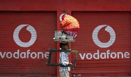 A vendor selling ''paani puri'', a traditional Indian snack, walks past closed shops displaying an advertisement for Vodafone in Jammu May 22, 2012. REUTERS/Mukesh Gupta
