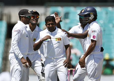 Team mates congratulate Sri Lanka's Rangana Herath (C) after he dismissed Australia's Mitchell Starc during the third day's play of the third cricket test match at the Sydney Cricket Ground January 5, 2013. REUTERS/Tim Wimborne