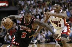 Nate Robinson, des Chicago Bulls (à gauche), à la lutte avec Norris Cole, du Miami Heat. Les Bulls se sont imposés 96-89 vendredi sur le terrain de la franchise floridienne, tenante du titre de NBA. /Photo prise le 4 janvier 2013/REUTERS/Andrew Innerarity