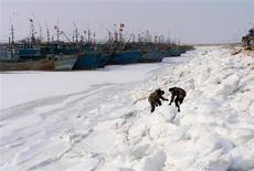 Las temperaturas en China han caído a su mínimo en casi tres décadas, lo bastante frío como para congelar las aguas costeras y atrapar a 1.000 barcos en el hielo, según dijeron medios oficiales el fin de semana. En la imagen, soldados inspeccionan un puerto donde las embarcaciones se han quedado atrapadas en el hielo, en Yingkou, en la provincia de Liaoning, el 4 de enero de 2013. REUTERS/China Daily