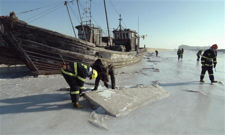 Investigators inspect a port where ships are stranded in ice, in Jinzhou, Liaoning province, January 5, 2013. REUTERS/China Daily