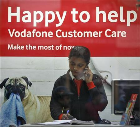 An employee talks on mobile phone inside a Vodafone store in Agartala, capital of India's northeastern state of Tripura, January 20, 2012. The Supreme Court ruled in favour of Vodafone Group Plc in its fight against a $2.2 billion tax bill, a decision analysts said would encourage foreign investment and clear the way for the company's planned initial public offering in India. REUTERS/Jayanta Dey (INDIA - Tags: BUSINESS TELECOMS)