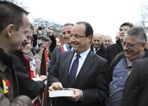 France's President Francois Hollande (C), flanked by Foreign Minister and local representative Laurent Fabius (C Rear), Val-de-Reuil's Mayor Marc-Antoine Jamet (L Rear) and French Minister for Industrial Recovery Arnaud Montebourg (R Rear), talks with Swiss Petroplus Petit-Couronne refinery workers in Val-de-Reuil, near Rouen, January 5, 2013. REUTERS/Charly Triballeau/Pool